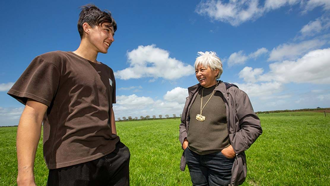Two people smiling together, standing outside in a field.