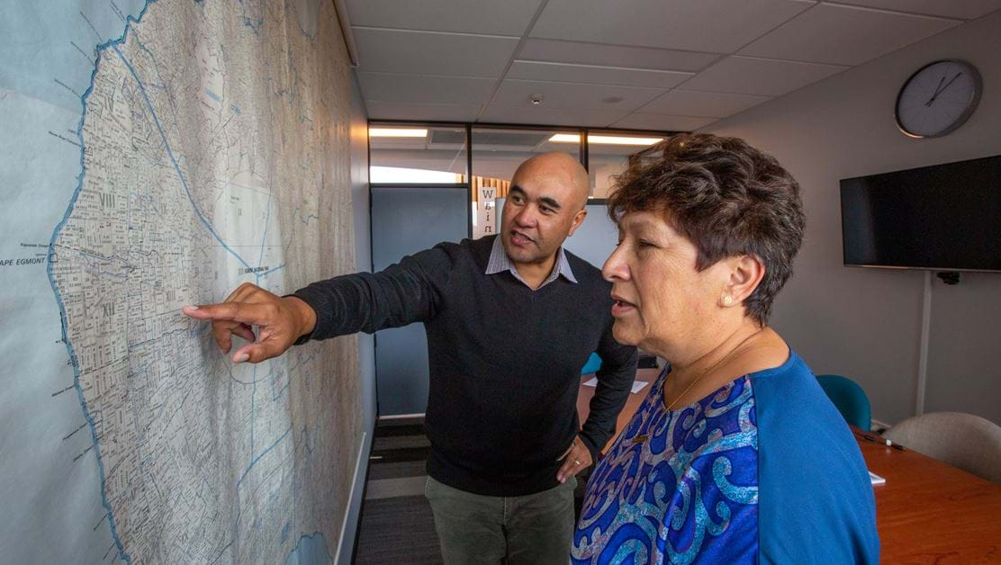 Two people looking at a map on the wall.