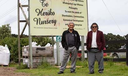 Two men standing in front of a sign for Te Heriko Nursery.